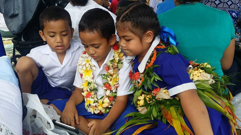 Tongan children with a device..