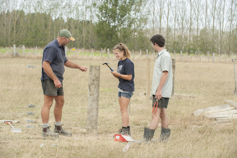 Two young people being shown a fence post by an older man..