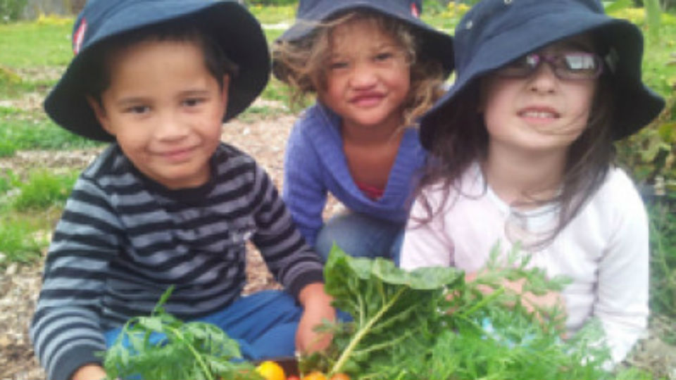Three children in the vegetable garden..